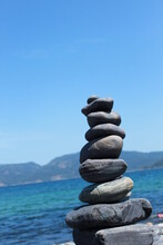Stack Of Pebbles In Sea Against Clear Sky