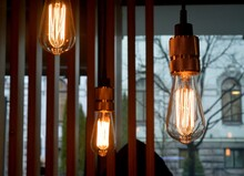 Close-up Of Illuminated Light Bulbs Hanging In Cafe