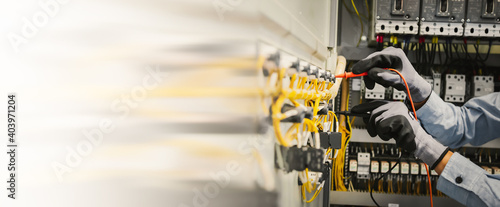 Photo Electrical engineers test electrical installations and wiring on protective relays, measuring them with a multimeter