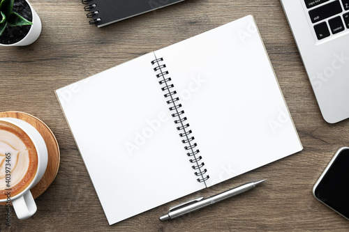 Obraz Blank notebook with pen are on top of wood office desk table with laptop computer, cup of coffee and suplpies. Top view with copy space. Morning life working from home concept. - fototapety do salonu