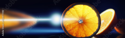 Fototapeta Composition with orange and grapefruit slices on a black background. A slice of orange with back light on a black background with water drops. Juicy orange on a table. obraz
