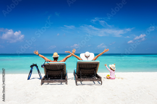 Tablou Canvas Happy family in sunbeds enjoys their vacation on a tropical beach with turquoise