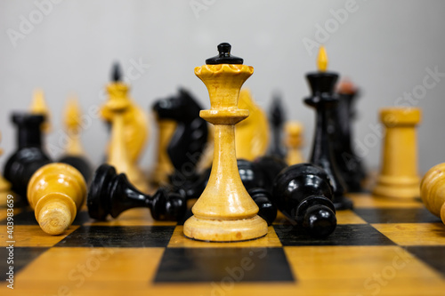 Fotografiet Vintage wooden chess on a chessboard in close-up.