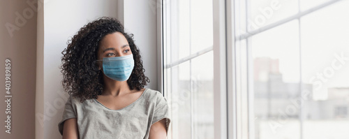 Canvas Print Sad woman alone during coronavirus pandemic wearing face mask indoors at home for social distancing panoramic banner