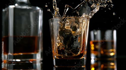 Photo Ice Cube falling into Glass of Whisky, Freeze Motion.