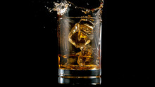 Ice Cube Falling Into Glass Of Whisky, Freeze Motion.