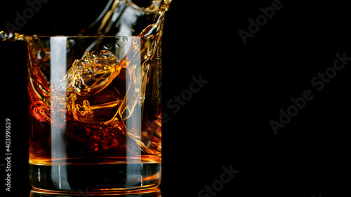 Fotografie, Obraz Ice Cube falling into Glass of Whisky, Freeze Motion.