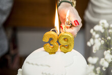 Closeup Shot Of A Woman Lighting Up The Number 39 Candles On A Cake
