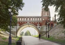 Road Under The Figure Bridge In Tsaritsyno. Decorative Bridge In The Palace And Park Ensemble Of The XVIII Century, Architect Vasily Bazhenov. Red Brick, Stone Arch, Street Lights, Gothic Stylization