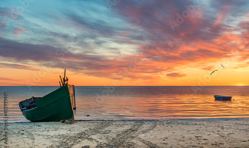 Anchored on sandy beach fishing boats near a small village of fishermen; here, at the Baltic Sea, traditional and mighty Baltic fisheries was successfully developed in 19-20-th centuries