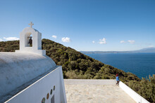 View Of Woman Standing On The Edge Of The Small Chapel Of Saint Alexander In Skiathos Island, Greece