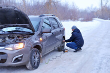Man Checking Air Pressure And Filling Air In The Tires With Car Eletric Pump On Road In Winter On A Snowy Path In The Forest Using A Pump. Broken Cars Concept
