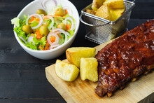Barbecue Ribs And Potatoes On A Wooden Board. Coy Space.
