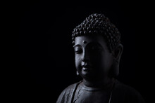 Meditating Buddha Statue Isolated On Black Background. Copy Space.