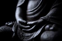 Hands Of Meditating Buddha Statue Isolated On Black Background.