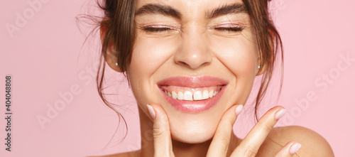 Fototapeta Close up of happy young woman with fresh glowing skin tone, showing beautiful white smile and grinning carefree, happy about valentines day, standing on pink background obraz