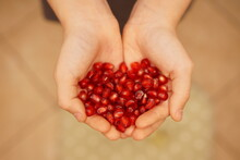 Cropped Hands Holding Pomegranate Seeds