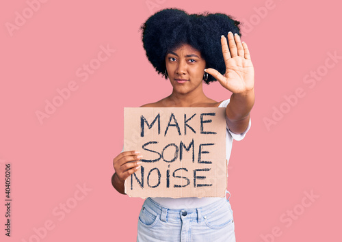 Foto Young african american girl holding make some noise banner with open hand doing