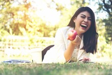 Cheerful Young Woman Lying With Apple On Lawn