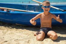 A Young Boy In A Blue Boat On The Ocean. A Child In Sunglasses On The Beach Near The Shore.