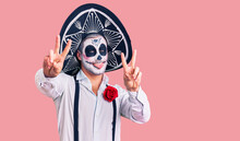 Man Wearing Day Of The Dead Costume Over Background Smiling With Tongue Out Showing Fingers Of Both Hands Doing Victory Sign. Number Two.