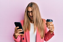 Young Blonde Woman Using Smartphone And Drinking A Cup Of Coffee Angry And Mad Screaming Frustrated And Furious, Shouting With Anger. Rage And Aggressive Concept.
