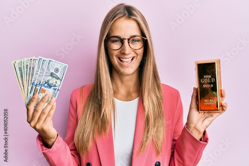 Canvas Print Young blonde woman wearing business style holding gold ingot and dollars smiling and laughing hard out loud because funny crazy joke