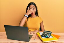 Young African American Girl Working At The Office With Laptop And Calculator Peeking In Shock Covering Face And Eyes With Hand, Looking Through Fingers With Embarrassed Expression.