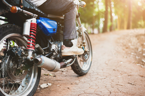 The motorcycle is driving on a dirt road in the forest Fototapet