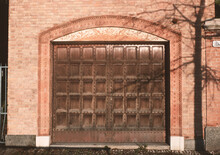 Garage In An Old Brick House With Large Studded Wooden Access Door And Decorated Frame.External Architectonic Object Of Building Structure.
