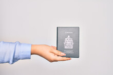 Hand Of Caucasian Young Woman Holding Canada Canadian Passport Document Over Isolated White Background