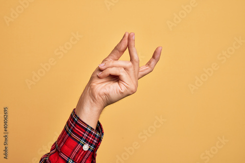 Leinwand Poster Hand of caucasian young man showing fingers over isolated yellow background snap