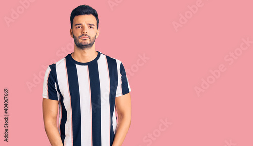 Obraz na plátně Young handsome hispanic man wearing striped tshirt skeptic and nervous, frowning upset because of problem