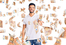 Young Handsome Hispanic Man Wearing Casual Clothes Smiling Cheerful Offering Palm Hand Giving Assistance And Acceptance.