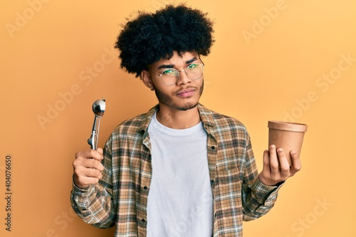 Fototapeta Young african american man with afro hair holding ice cream and ice cream scoop skeptic and nervous, frowning upset because of problem