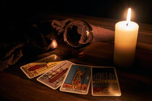 Concept Of Fortune-telling Wooden Table And White Candle With A Crystal Ball And Tarot Cards On Dark Background