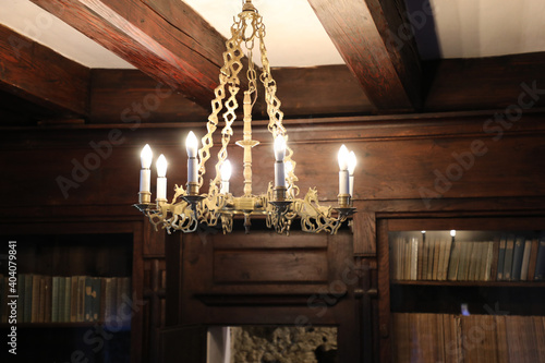 Foto old beautiful chandelier with candles on the background of wooden cabinets with