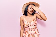Young Beautiful Latin Woman Wearing Summer Hat Surprised With Hand On Head For Mistake, Remember Error. Forgot, Bad Memory Concept.