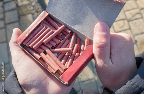 Fototapeta Young caucasian boy holding a box with small firecrackers or petards in his hand