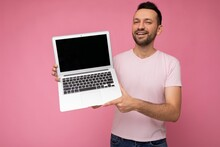 Handsome Smiling Brunet Man Holding Laptop Computer Looking At Camera In T-shirt On Isolated Pink Background