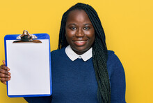 Young Black Woman With Braids Holding Clipboard With Blank Space Looking Positive And Happy Standing And Smiling With A Confident Smile Showing Teeth