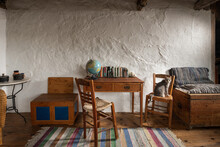Front View Of Vintage Room Interior In Traditional Village Country House. Old Handmade Furniture, School Desk, Wooden Chairs, Craft Chest On Stucco Wall Background
