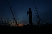 Silhouette Man Photographing Field Against Sky At Sunset