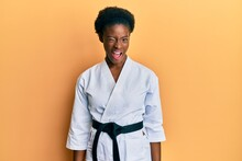 Young African American Girl Wearing Karate Kimono And Black Belt Winking Looking At The Camera With Sexy Expression, Cheerful And Happy Face.