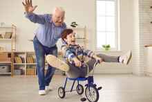 Healthy Senior Man Joins Carefree Childish Game. Grandfather And Grandson Playing Together, Riding Tricycle, Fooling Around, Having Fun. Happy Family Enjoying Free Time On Weekend At Home, Candid Shot