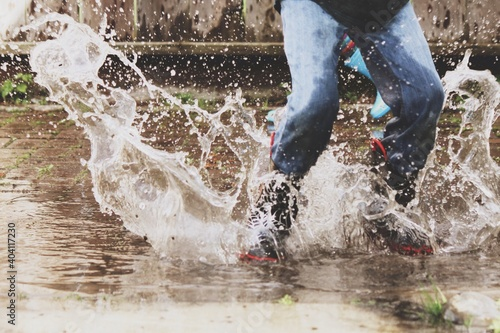 Fotografie, Obraz Low Section Of Man Jumping On Puddle