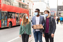 Happy Friends Wearing Masks With Takeaway Pizza In London During Lockdown - Multiracial Group Of Best Friends Having Pizza At Home Due To Coronavirus Restrictions