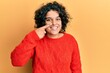 Leinwandbild Motiv Young hispanic woman with curly hair wearing casual winter sweater pointing with hand finger to face and nose, smiling cheerful. beauty concept