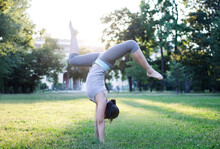 Full Length Of Young Woman Doing Handstand In Park