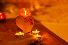 Wooden Heart And Candles On Burlap And Wooden Boards. St Valentine's Day Greeting Card With Candle And Heart On A Blurred Background. Love Story Concept. Copy Space